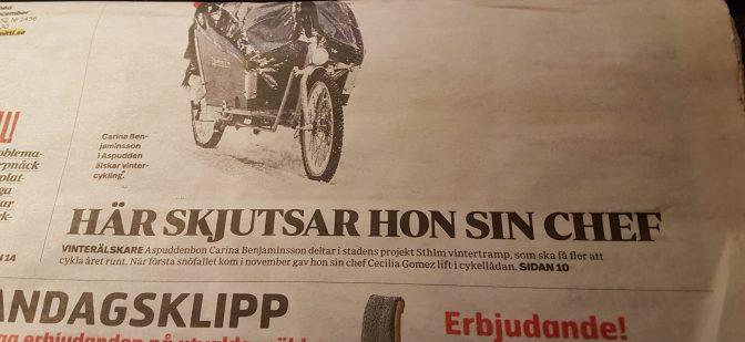 """Dubbelvikt tidning med rubrik """"Här skjutsar hon sin chef"""" under en halv bild. På bilden syns ett flerhjuligt fordon och nederkanten av ett regnplagg."""