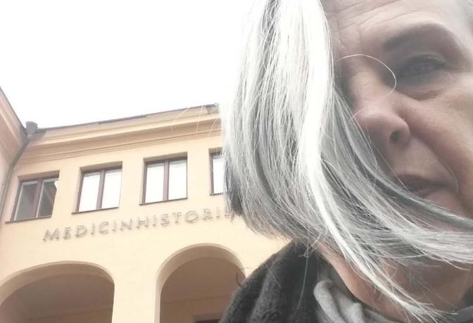 """Jag sitter framför Eugeniahemmets byggnad. På dess fasad syns början av texten """"Medicinskhistoriska museet"""""""