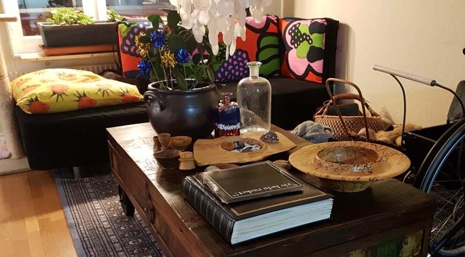 Hörn av mitt vardagsrum med kuddar, soffa, bord med böcker, vaser och blomma. Rullstol och flätade korgar på golvet bredvid.
