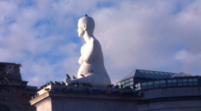 En skulptur av en kvinna utan armar om är höggravid sitter högt upp i solen på en marmorkolonn